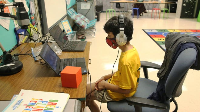 Nova Blanche Forman Elementary School teacher Attiya Batool, teaches her 4th grade class virtually as her son, Nabeel, does his second grade classwork online wearing a face mask and headphones during the first day of school in Broward, Wednesday, Aug. 19, 2020, in Davie, Fla. All classes in Broward public schools are being taught remotely. The school district has made some adjustments where teachers may bring their child to their classroom to do remote learning while they teach their students under certain conditions.