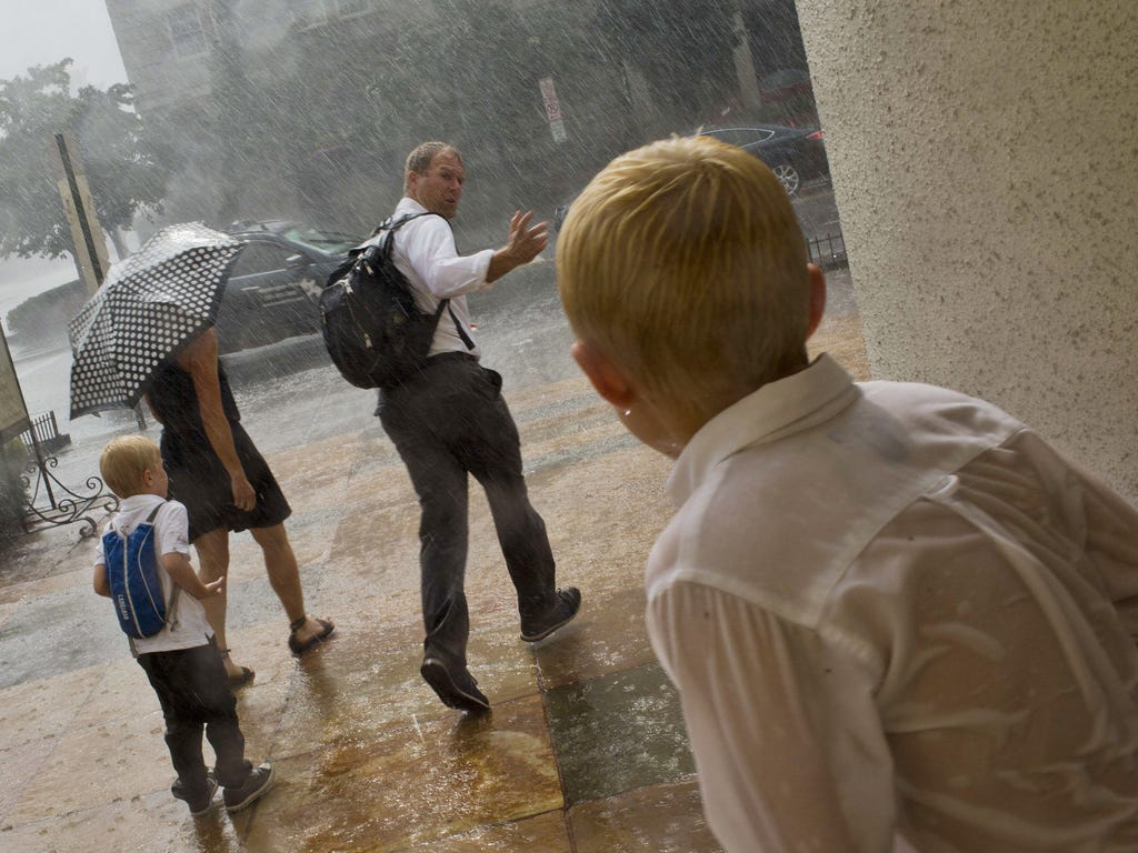 A father calls to his son as they run out to the curb to grab a taxi during a heavy rainstorm in Washington, D.C.