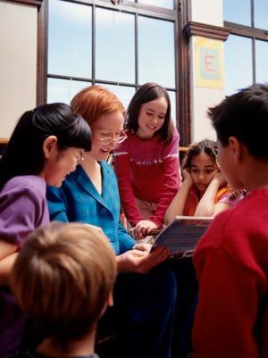 A teacher reads a book to children in a school classroom