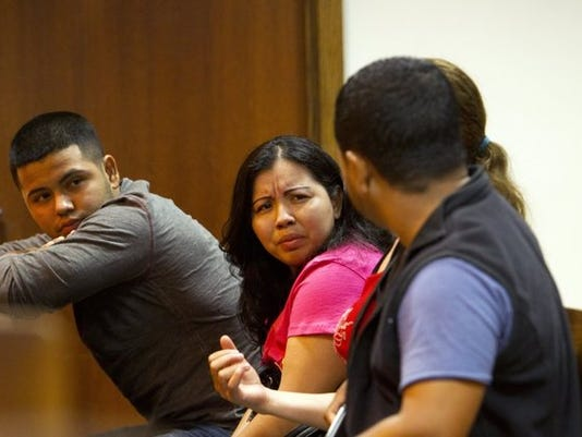 Enma Garcia and her relatives exchange looks during a first appearance for Garcia's boyfriend, Jose A. Rico, at the Collier County courthouse on July 18, 2014. A state attorney said Rico, arrested Wednesday at the Incredible Fresh Fruit Dynamics raid, had previous out-of-state arrests, a fact that his relatives and friends disputed. (Carolina Hidalgo/Staff)