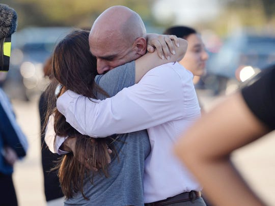 Families reunite after a mass shooting at nearby Marjory