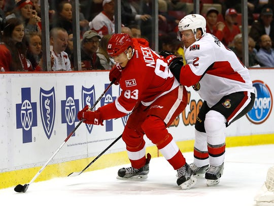 Red Wings forward Tomas Nosek tries to get control of the puck in front of the Senators' Dion Phaneuf during the first period Monday at Joe Louis Arena.