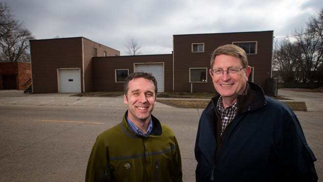 Derek Lord, Ankeny economic development director, and John Peterson, former Ankeny community development director, stand in front of vacant properties across the street from Firetrucker Brewery in March 2015.
