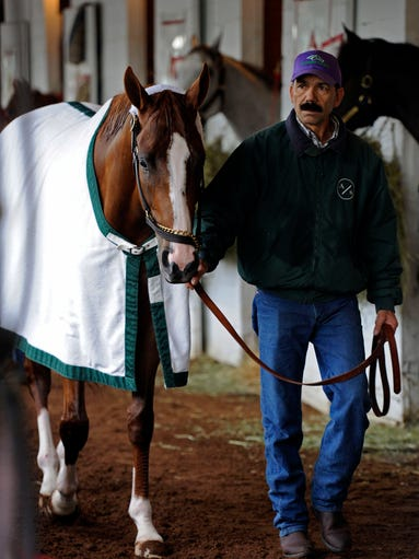 Groom Raul Rodriguez walks Kentucky Derby hopeful California Chrome during morning workouts at Churchill Downs.