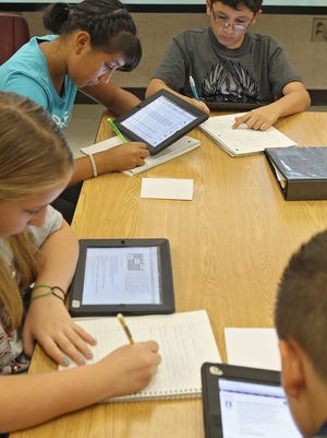 Seventh-grade students at Cahuilla Desert Academy in Coachella use iPads in science class.