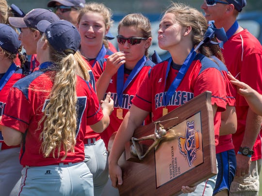 Tecumseh's Kierra Schoenbaechler holds the trophy after beating the Tri Titans in their Class A state championship softball game at Ben Davis High School Saturday morning.