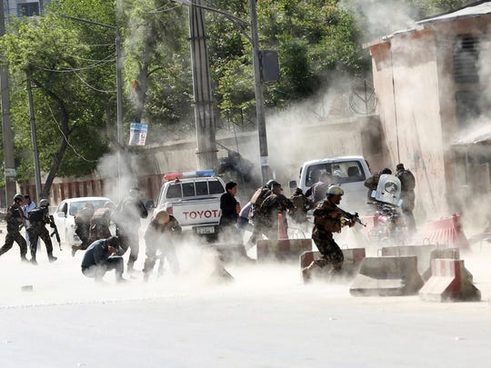 Afghan security forces run from the site of a suicide attack after the second bombing in Kabul on April 30.