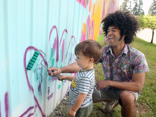 Cory Bennett, right, helps Olsen Fisher, 3, paint part of a heart at the Poulsbo Community Mural on Thursday.