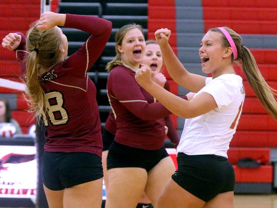 Riverdale's Kaiya Todd (18) and Sarah Jones (16) celebrate a point with other teammates during the game against Stewarts Creek on Tuesday, Aug. 30, 2016.