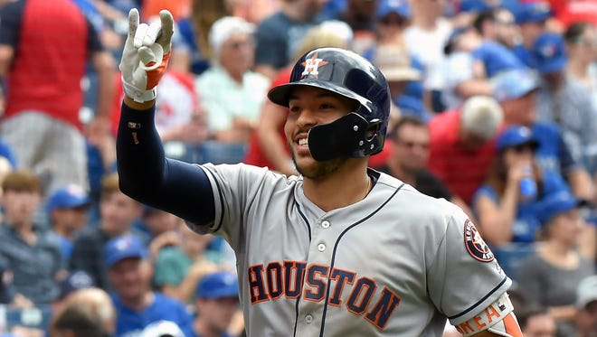 Carlos Correa gestures as he celebrates hitting a three run home run.
