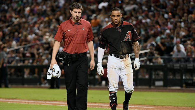 Jun 30, 2018; Phoenix, AZ, USA; Arizona Diamondbacks infielder Ketel Marte (4) is assisted off the field by head athletic trainer Ryan DiPanfilo (left) after suffering an apparent injury in the seventh inning against the San Francisco Giants at Chase Field. Mandatory Credit: Jennifer Stewart-USA TODAY Sports