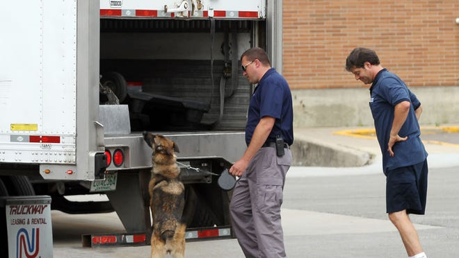 A dog sniffs the interior of a tractor trailer making a delivery to the IRS in Covington after white powder in an envelope resulted in a hazmat scare.  The powder was harmless and there were no injuries.