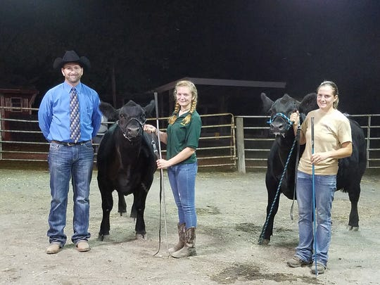 Beef judge Bradley Gill, of Newport, and the Grand Champion and Reserve Champion Beef steers, both exhibited by Kristen Feeser of New Oxford. Also pictured is Missy Jeffcoat, 4-H Beef Club leader.