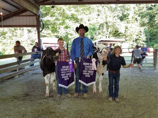 Mason Nas with his Grand Champion Dairy Beef Feeder Calf, judge Bradley Gill, and Katelyn Keller's Reserve Champion Dairy Beef Feeder Calf.