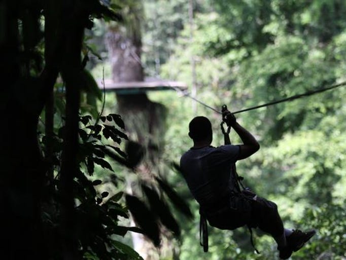 A ziplining guide crosses over to the next platform before helping students zipline through the rain forest canopy as one of the activities during their trip to the Osa Peninsula in Costa Rica.