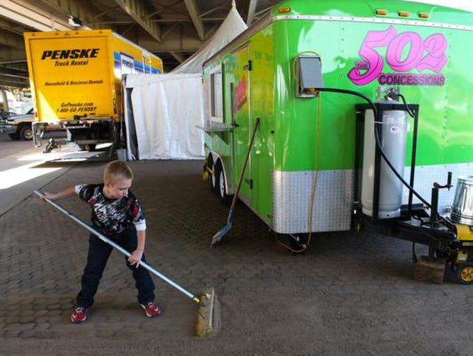 Cameron Osman, 11, sweeps the area near his father's 502 Concessions booths as they prepare for the weekend Thunder event. April 11, 2014
