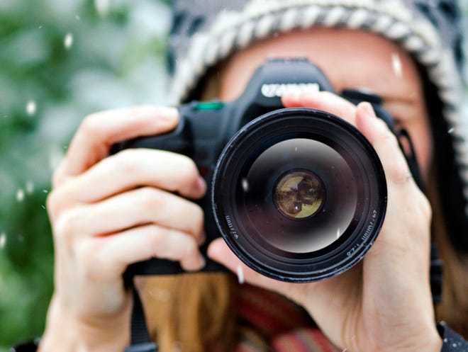 Stock photo of woman taking picture in snow (to camera) Credit: Caroline Purser, Getty Images GETTY ID#: 84935885