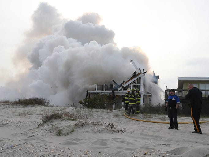 Firefighters work the scene where three homes were destroyed by a fire that broke out near the beachfront, Friday, April 18, 2014, in Sea Isle City, N.J. Authorities say no injuries have been reported in the smoky fire, which erupted around 4:30 p.m. Friday and sent large clouds of black smoke spewing across the region. It was brought under control about two hours later.