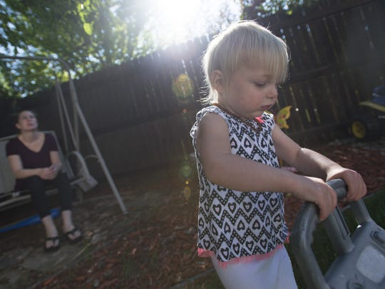 Ashlyn Baird sits on a swing while her daughter, Kylie,