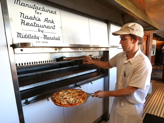 Noah's Ark Ristorante began it's Des Moines presence in 1946 and has built generations of loyal customers. Dustin Dixson brings a supreme pizza out of the oven.