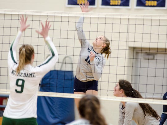 Marysville's Hayley Delor (12) hits the ball over the net while Pontiac Notre Dame's Gabrielle Shilling (9) blocks during the MHSAA Class B Regional Semifinal volleyball game at North Branch High School Nov. 7.