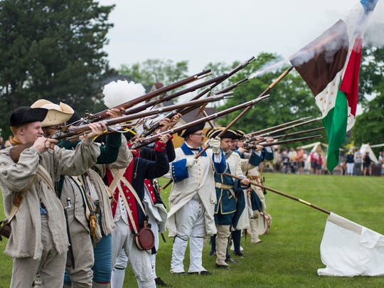 American and French army reenactors fire their rifles during the opening ceremony of the Feast of the Ste. Clair Saturday, May 26, 2018 at Pine Grove Park in Port Huron.