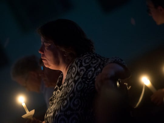 In this file photo from March 4, 2014, people gather during a candle light vigil for families with students who attend Dover Area School District at Dover Bethany Church. The vigil was a response to the arrest of music teacher, Matthew Puterbaugh.