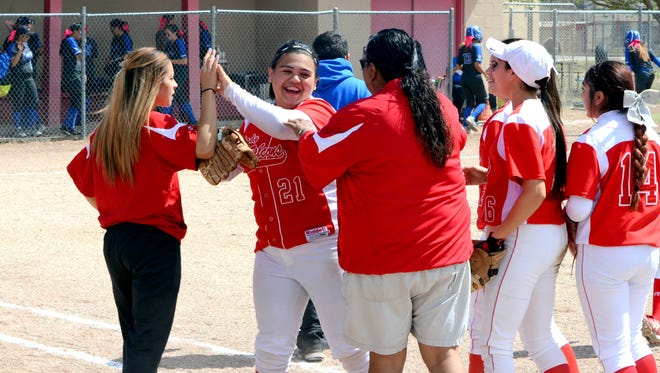 Loving celebrates a double play made by senior first baseman Clarissa Calderon (21) Thursday, March 31 against Dexter. Calderon was named to the first all-state 3A team.