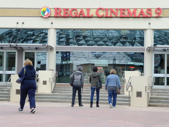 Potential moviegoers check out the Regal Cinemas that