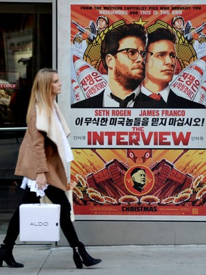A woman walks past a poster for the film 'The Interview' outside a theater in New York on Dec.18, 2014. Sony Pictures canceled the film's Christmas Day release.