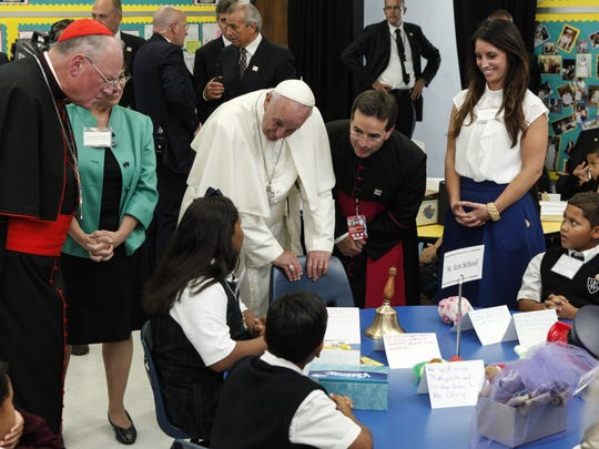 Pope Francis speaks with children while visiting a classroom in Our Lady Queen of Angels School in East Harlem, in New York, September 21, 2015.