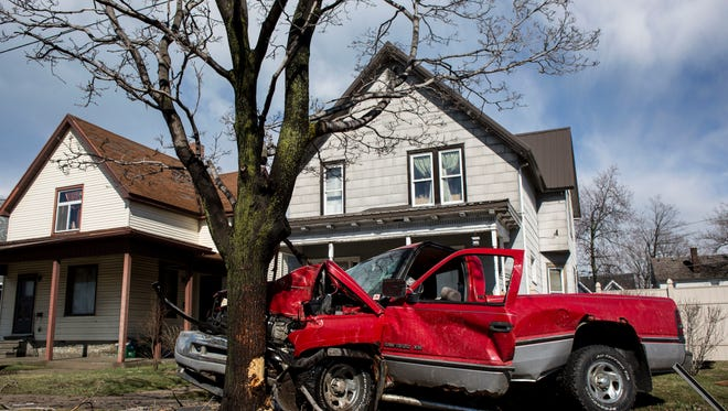 Members of the Port Huron police and fire departments work the scene where a truck crashed through two street signs an into a tree Wednesday on Pine Grove Avenue in Port Huron. The man driving the truck was transported to McLaren Port Huron with injuries that did not appear to be life threatening.