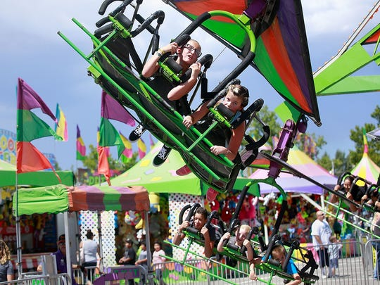 In this file photo, Daydre Silva, 10, left, and Pixie Littlefield, 10, of Aztec, ride the Cliff Hanger during a previous San Juan County Fair McGee Park.