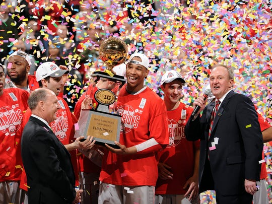 Ohio State's Jared Sullinger lifts up the Big Ten Men's Tournament trophy as head coach Thas Matta has a word for the fans after the Buckeyes defeated Penn State 71-60.
