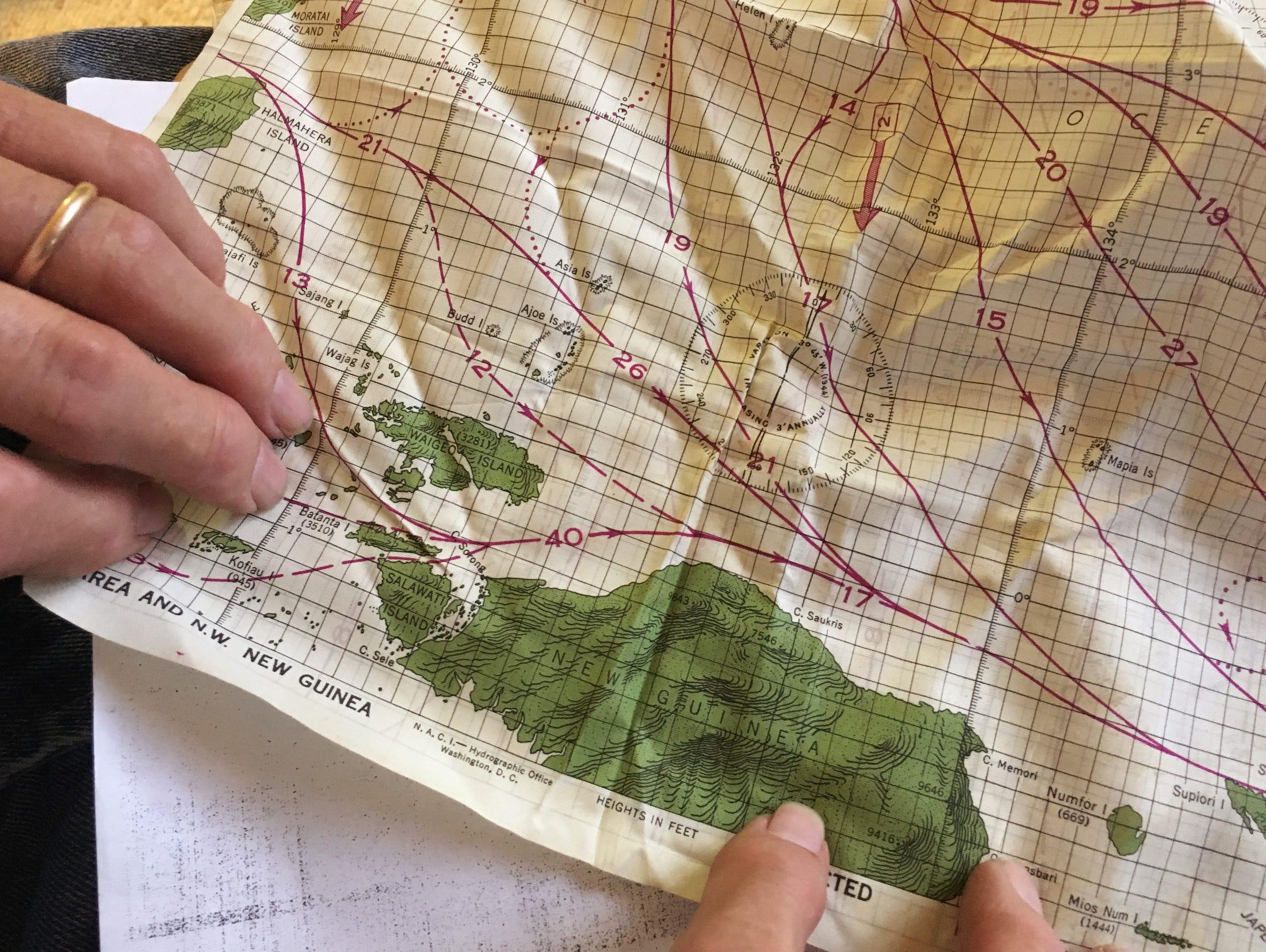 Leo Bundschuh hold a silk map of New Guinea he kept