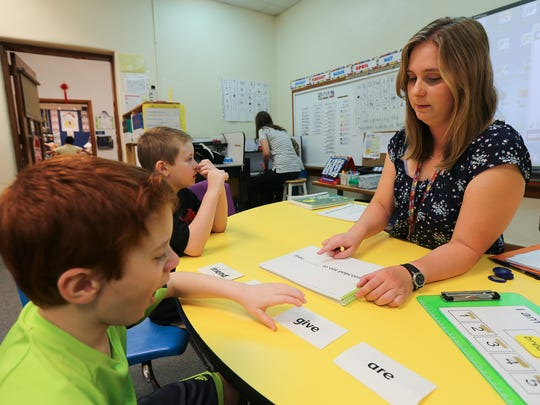 Field Elementary teacher Jessica Rockhold works on reading with Tyler Howard, background, and Anthony Diaz, foreground.