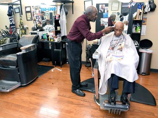 Vernon Winfrey cuts Leroy McMurray's hair at Winfrey's