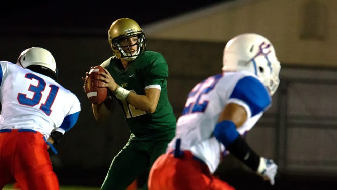 Iowa City West's Alex Henderson (12) looks to pass against Davenport Central during the first half of play in Iowa City on Friday, September 25, 2015.