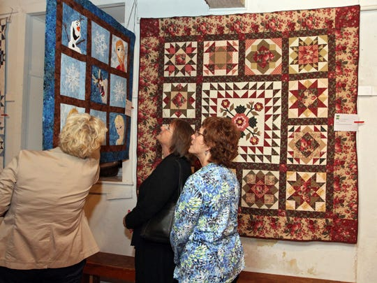 (l-r) M.C. Hart, Flemington, Donna Harrold, of Pittstown, and Annie Palumbo, of Easton, Pa, looks at the display of quilts during a show held by the Courthouse Quilters, at the Prallsville Mills in Stockton, Oct. 2, 2014.