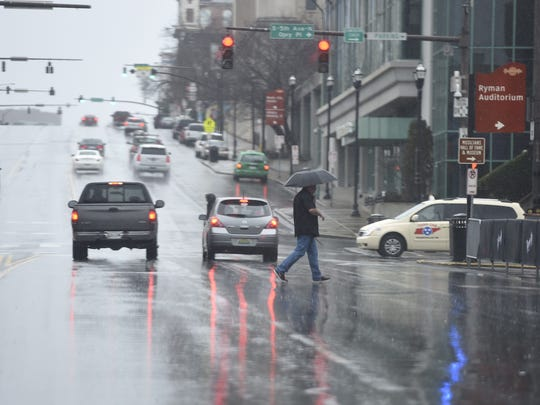 A pedestrian makes his way across Broadway as it rains Tuesday March 1, 2016 in Nashville, Tenn.