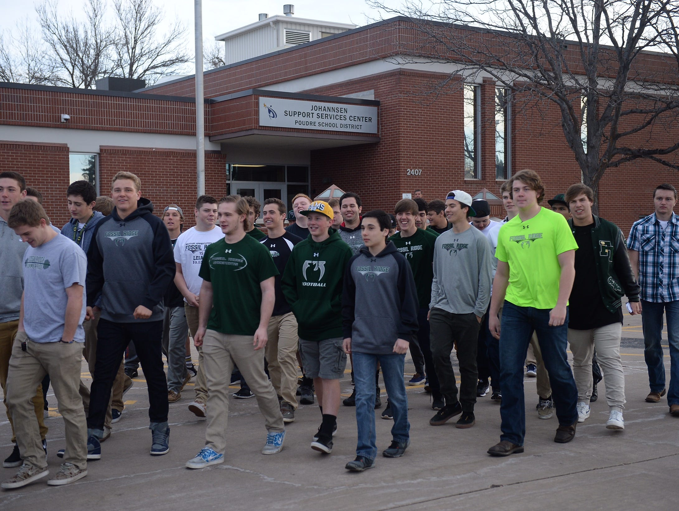 Fossil Ridge football players leave the PSD Support Services building after delivering letters showing support for coach Brian Tinker after he was fired on Friday.