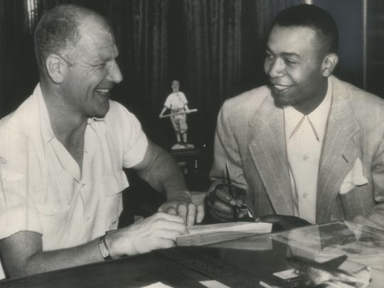 The second African-American player to get into the major leagues and the first in the American League, Larry Doby (right) signs a Cleveland contract on July 5, 1947, in Chicago with Bill Veeck, president of the Indians.
