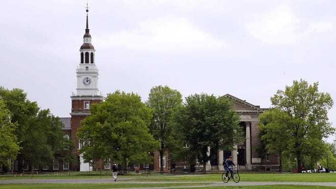 Students cross The Green in front of the Baker-Berry Library at Dartmouth College in Hanover.