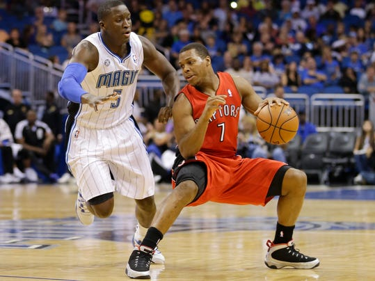 Toronto Raptors guard Kyle Lowry (7) makes a move to get around Orlando Magic's Victor Oladipo (5) during the first half of an NBA basketball game in Orlando, Fla., Sunday, March 30, 2014. (AP Photo/John Raoux)