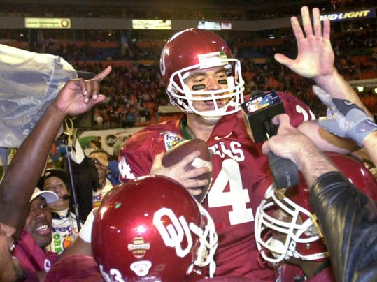FILE - In this Jan 3, 2001 photo, Oklahoma quarterback Josh Heupel celebrates with teammates after they defeated Florida State 13-2 in the BCS championship NCAA college football game at the Orange Bowl in Miami Gardens, Fla. Heupel, who has been the offensive coordinator/quarterbacks coach at Missouri the past two seasons, was hired Tuesday, Dec. 5, 2017, as UCF's new football coach.  (Tom Gilbert/Tulsa World via AP)