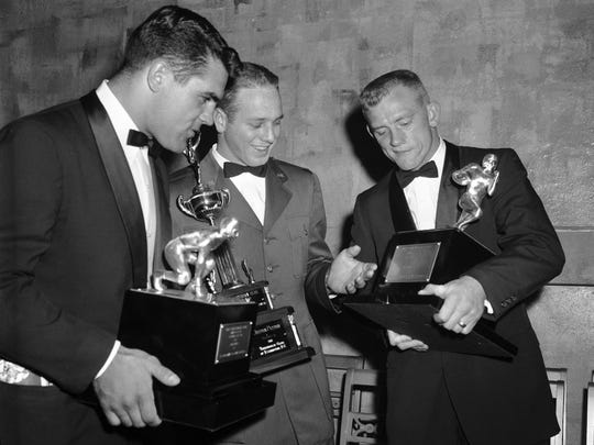 Kentucky's Lou Michaels, left, holds the Knute Rockne Trophy, which he received from the Touchdown Club of Washington as the outstanding college lineman for the 1957 season in this Jan. 11, 1958, file photo. Also in the photo are Lt. Huston Patton, USAF, center, who was named outstanding armed forces player; and Texas A&M's John David Crow, who received  the Walter Camp Memorial Trophy as the outstanding college back. Michaels, a  College Football Hall of Famer, died Jan. 19. He was 80.