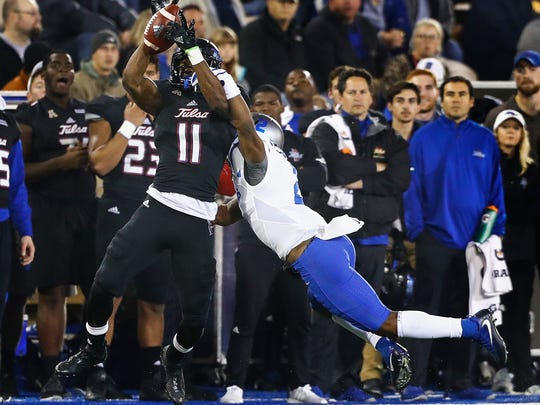 University of Tulsa receiver Nigel Carter (left)  grabs a catch in front of University of Memphis defender Tito Windham (right) during first quarter action in Tulsa, Okla., Friday, November 3, 2017.