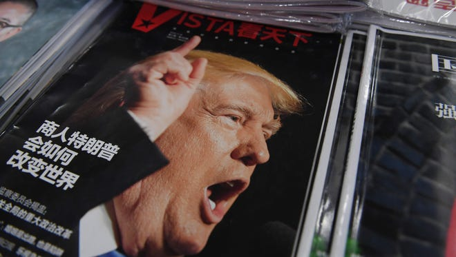 """A magazine featuring President-elect Donald Trump is seen at a bookstore in Beijing on Dec. 12, 2016.   The headline reads """"How will businessman Trump change the world."""""""
