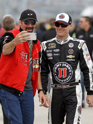 A race fan takes a selfie with Kevin Harvick, right, before Sunday's pole qualifying for the 2016 Daytona 500.