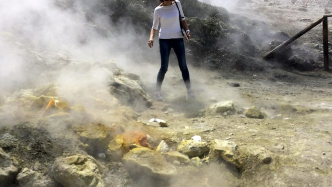 In this photo taken on Saturday, April 30, 2016, a woman takes a close look at a steaming fumarola at the Solfatara crater bed, in the Phlegraean Fields near Naples, Italy. Fields – Campi Flegrei in Italian – are a sprawling constellation of ancient volcanic centers.